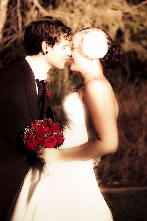 infatuation: Funky Young Married Couple Laugh And Kiss With Red Rose Bouquet Showing Their Love And Infatuation For One Another  On Their Wedding Day