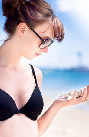 young beautiful woman: Portrait Of A Beautiful Young Woman Studying Marine Life In The Form Of A Sea Star At An Outdoor Picturesque Beach Location Stock Photo