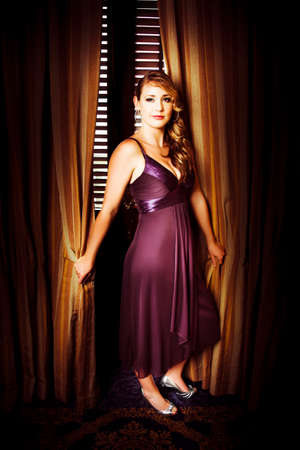 stardom: Beautiful actress wearing a purple evening dress with long curly blonde hair posing in front of ornate gold curtains for her portrait at the premiere of her latest film