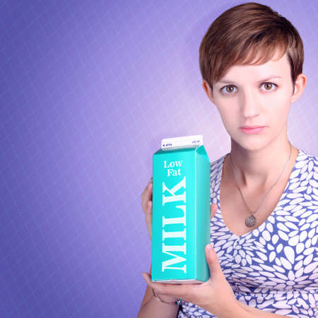 fat food: Woman with serious expression holding carton of low fat milk on purple design interior. Fat debate Stock Photo