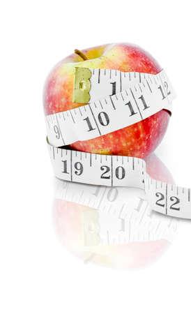cinta metrica: La dieta y el concepto de alimentación saludable de una manzana roja con cinta métrica aislado en el fondo blanco