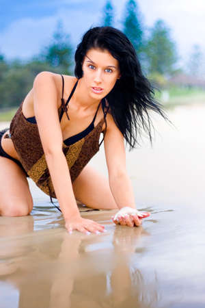 dismayed: Beautiful Young Woman Wearing Swimsuit Holding Seashell Exploring The Shallow Edge Of The Ocean Water As Her Hair Blows In The Beach Breeze Stock Photo
