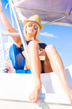 seafaring: Beautiful Blond Female Tourist Wearing Swimmers Hat And Sunglasses Sitting On A Boat While On A Holiday Or Vacation Sightseeing Tour