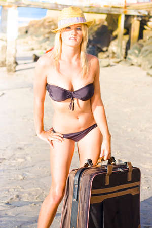 just arrived: Beautiful Young Woman Wearing Bikini Standing On The Beach With A Large Old-Fashioned Suitcase As If She Just Arrived