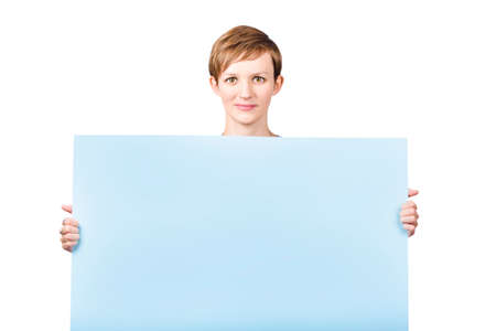 endorsement: Pretty pert young woman with a lovely warm smile holding a rectangular empty board with room for your product endorsement. isolated on white