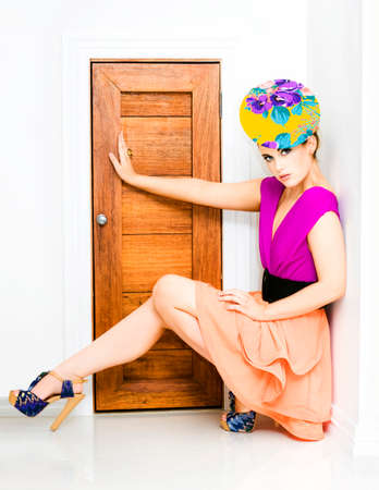 squatting down: Young trendy woman in colourful fashion outfit squatting down against a wall with her arm and leg extended out blocking a small doorway in a fashion police concept Stock Photo