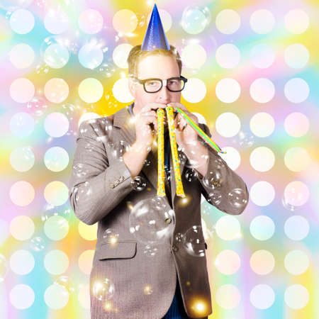 Creative portrait of a dorky new years eve man blowing celebration horns at a countdown party. Special occasion