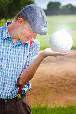 large ball: In A Golfing Illusion A Golfer Man Dreams Up Holding A Large Shiny Golf Ball That Would Be Impossible To Miss Off The Tee Off In The Golf Of Big Balls