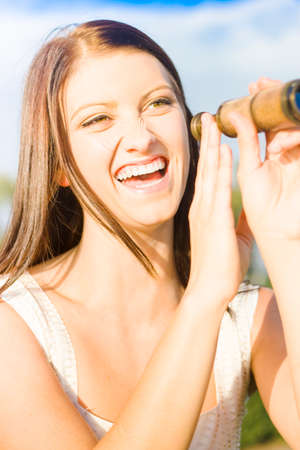 ocular: Funny Sight Concept With An Attractive Girl Laughing While Scouting The Skies With A Vintage Ocular Telescope Or Monocular