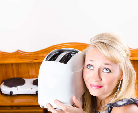 toaster: Good looking woman serving breakfast in home kitchen with toaster in morning meal concept