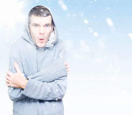 freeze: Blue copyspace portrait of a young man in hooded jumper freezing in the ice cold winter snow Stock Photo