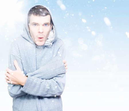 the weather: Retrato azul copyspace de un joven en el puente encapuchado congelación en el hielo frío invierno la nieve Foto de archivo