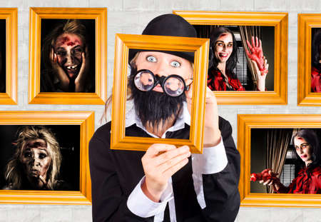 framed picture: Quirky photograph of a male art critic examining scary horror artworks inside a Halloween gallery display. Art of horror concept