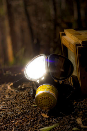 eyepiece: Sunlight Shinning Off The Glass Eyepiece On A War Gas Mask Breathing Apparatus Sitting Next To A Ammunition Box In A Reflection Of War