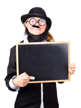 A smiling woman in mens clothes and fake beard with a blank blackboard. Humorous teacher concept