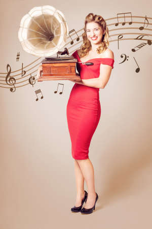 Cute vintage portrait of a trendy pinup woman in slim red dress holding old style gramophone music player on classical notes background. Pin-up at the disco