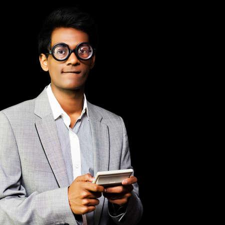 estereotipo: Imagen conceptual del empollón obsesivo por excelencia en gafas redondas magnificados descomunal jugar a un videojuego ordenador de mano