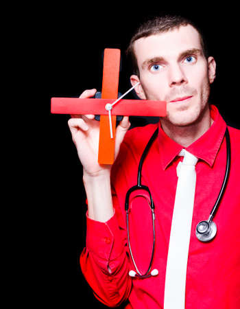 Serious Male Doctor Showing Cross Clock In A Display Of Health Check Time Over Black