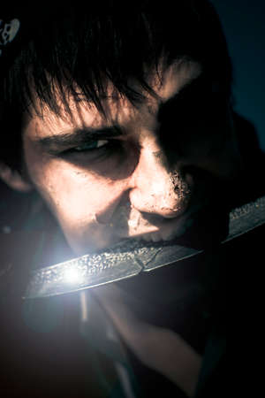 scarred: Terrifying Horror Face Portrait Of A Scarred And Blistered Pirate Biting On A Razor Sharp Sword Blade In A Frightening Fear And Danger Concept