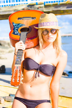 sassy: Young Sassy Female Performing Artist In Bathing Costume, Dark Glasses And Summer Fashion Hat Holding Acoustic Guitar At An Oceanic Port Stock Photo