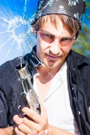 pirated: Break And Enter Concept Sees A Sinister And Deadly Burglar With Gun Look Though A Cracked And Broken Glass Window During A Violent Home Invasion Or Burglary Stock Photo