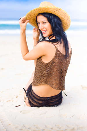 Beautiful Young Woman With Black Hair Smiling With Happy Expression Sitting On The Beach With Ocean Waves In Background