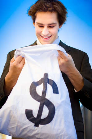 Excited And Happy Business Man Smiling While Looking Into A Dollar Sign Money Bag After A Business Deal Of Financial Reward And Success Stock Photo