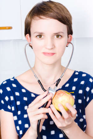 Attractive young woman doctor in blue dress holding stethoscope against an eating apple symbolic of maintaining good health