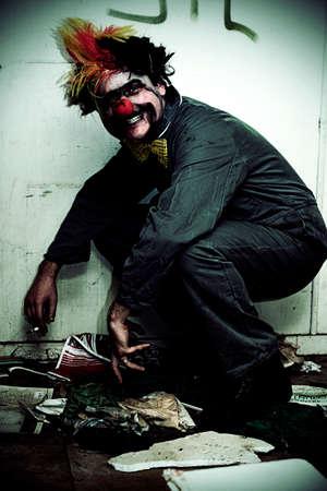 cuclillas: Sr. ocupante Los parados payaso sonr�e mientras se pone en cuclillas en una casa sucia vieja abandonada