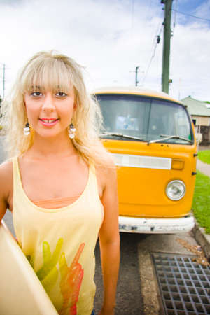 Vintage Surfer Portrait Taken On A Road In Front Of Retro VW Van With Happy Blond Surfing Woman Holding Surf Board