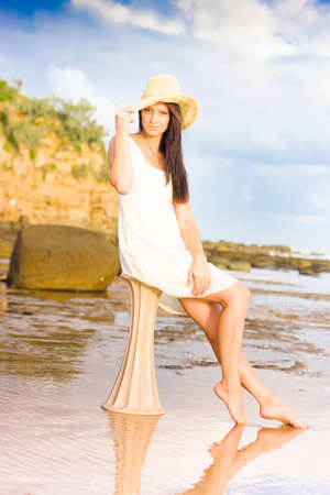 suncare: Fashion Shot Of A Beautiful Woman At The Beach Sitting On A Greek Style Pillar. White Sand Blue Cloudy Sky Stock Photo