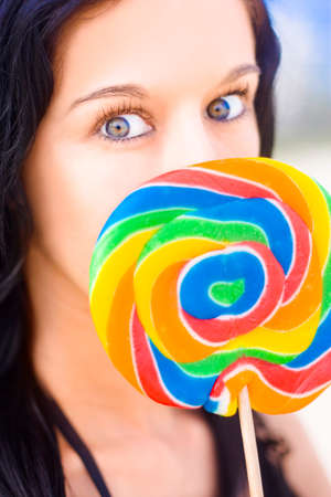 tantalizing: Attractive Young Woman With Vivid Multicolor Eyes Posing With A Pretty Rainbow Candy Lollipop Looking Possessed By A Love Of Candy