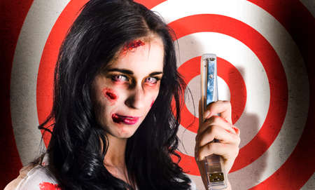 retribution: Angry dead businesswoman holding stapler while aiming to fire in a business target concept Stock Photo