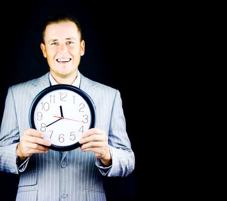 dapper: Smiling man in gray business suit holding a clock on black background with copy space Stock Photo