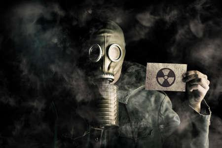 mascara de gas: concepto de la contaminación del medio ambiente con un hombre que llevaba una máscara de gas en una atmósfera contaminada de humo que soporta una tarjeta de identificación en blanco para identificarse a sí mismo bajo su engranaje protector usado para sobrevivir