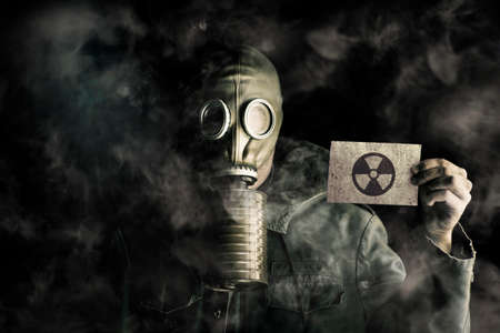 pollutants: Environmental pollution concept with a man wearing a gas mask in a smoky polluted atmosphere holding up a blank ID card to identify himself under his protective gear worn to survive