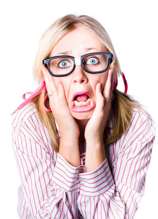 appalled: Attractive young blonde woman wearing nerdy glasses reacting in horror and fright with her eyes wide and her hands clawing at her face while her bottom lips juts out in a quiver, isolated portrait Stock Photo