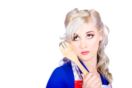 stiring: Delicious young blonde pinup model holding cooking spoon when stirring up thoughts for bright recipe ideas. Food copyspace concept