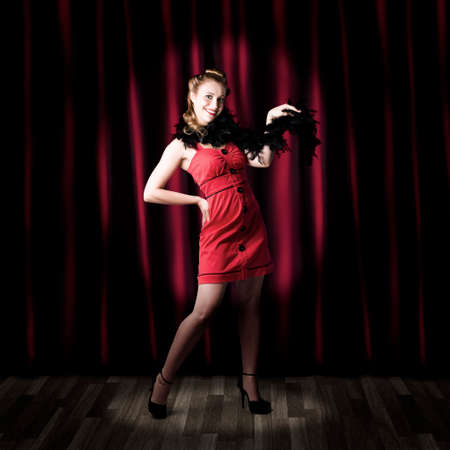 depiction: Showgirl Performing On A Theater Stage In Front Of Red Curtains In A Depiction Of A Broadway Cabaret Show Stock Photo