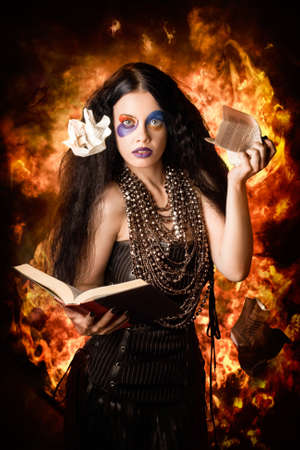 bewitchment: Female mystic ripping up and burning pages from a spell book. Black magic