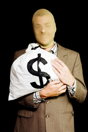 featureless: Grinning business man hiding under a stocking mask clutches a large money bag from his previous employer conceptual of a business or white-collar thief Stock Photo