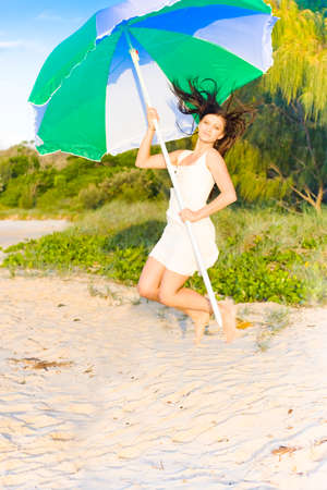 mini umbrella: Healthy Fit And Young Woman Jumping Outdoors At A Beach Location With A Umbrella In A Fun And Happiness Concept
