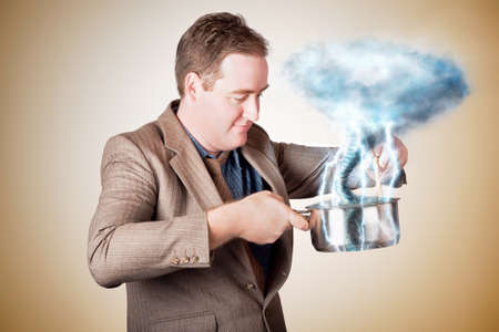 emanating: Planning business man standing in kitchen stirring up a storm of clouds and lightning from a saucepan when cooking up a storm Stock Photo