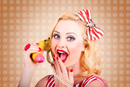 20 year old girl: Old-fashioned photograph of a surprised blond pin up woman listening in on a banana telephone. Women healthy eating news Stock Photo