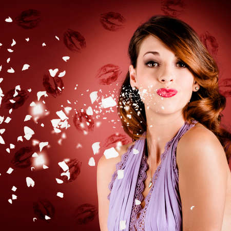 lipstick kiss: Lovely romantic pin-up girl blowing a valentine kiss with magical style while heart shape paper pieces float in the surrounding air. On lipstick kisses background