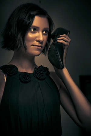 secret agent: Dark Portrait Of An Undercover Secret Agent Spy Holding Her Formal High Heel Shoe To Face When Using It As A Telephone While On A Covert Surveillance Mission