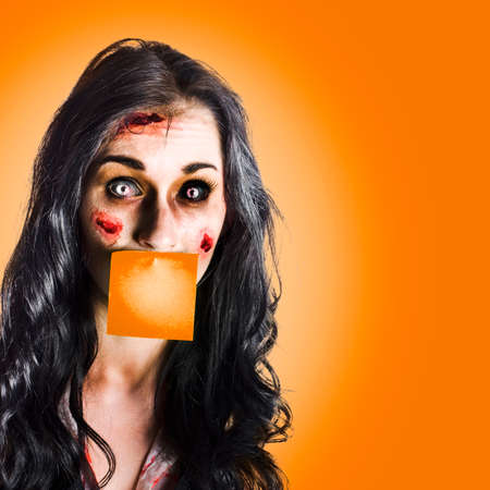 face work: Face of a female office assistant overworked to death with a orange sticky notepad over mouth in a hard work conceptual
