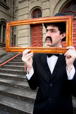 pensador: Enmarcando la escena de un pensador creativo sostiene un marco de madera para capturar una visión de la imagen Perfección