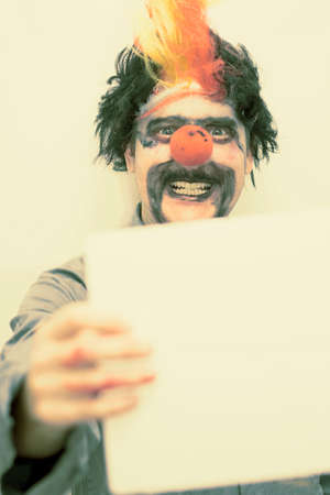 clowning: A Evil Clown Smiles With A Frightening Expression While Holding The Sign Of Vintage Horror