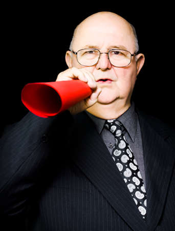 worthy: Elderly male protester or business leader rallying the masses to a worthy cause by making an important announcement through a megaphone of symbolic rolled red paper Stock Photo